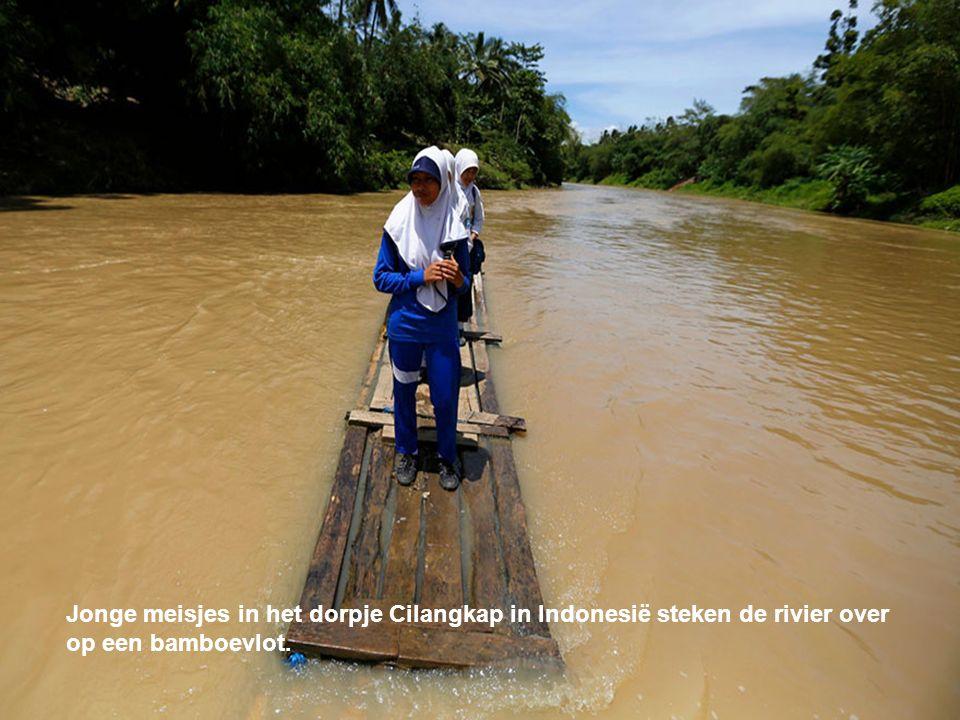 Jonge meisjes in het dorpje Cilangkap in Indonesië steken de rivier over op een bamboevlot.