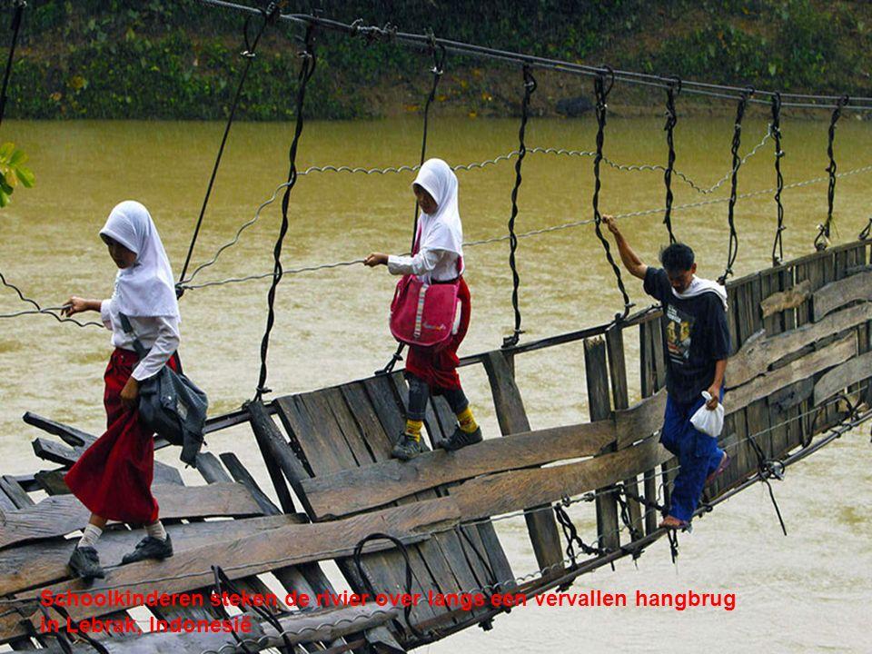 Schoolkinderen steken de rivier over langs een vervallen hangbrug