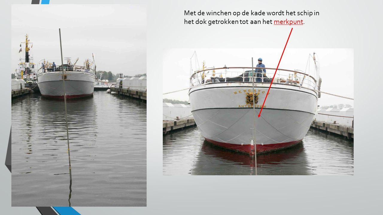 Met de winchen op de kade wordt het schip in het dok getrokken tot aan het merkpunt.